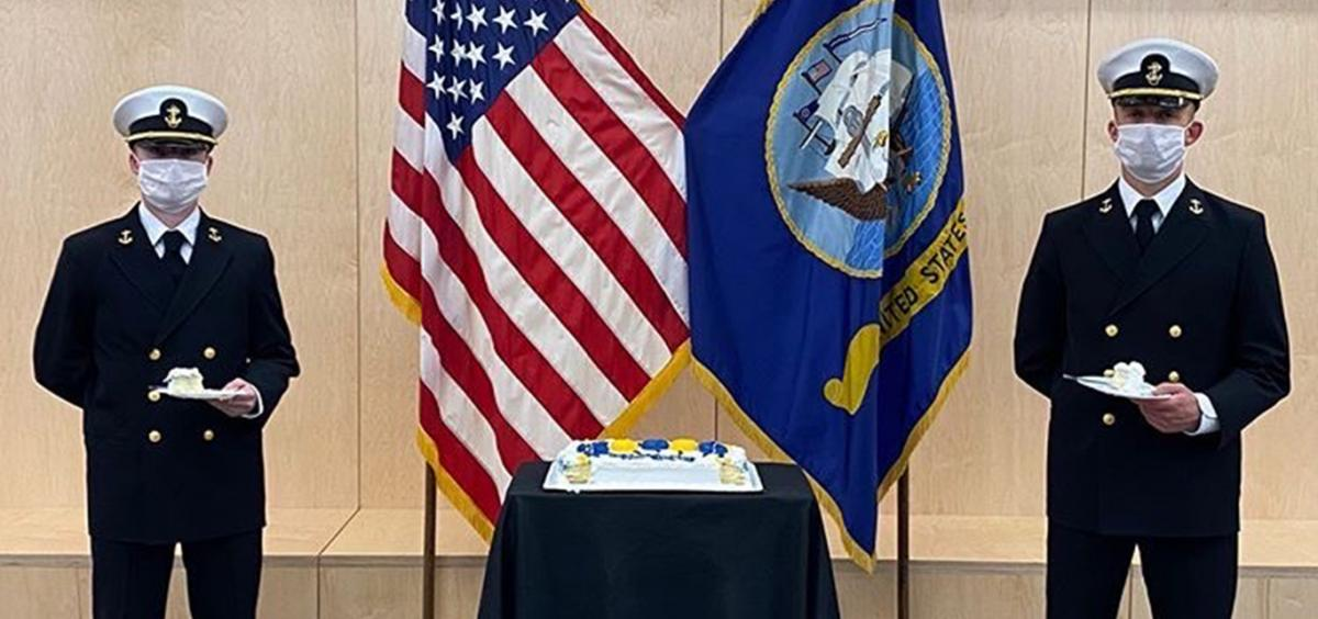 Two Midshipmen stand at attention next to a birthday cake.